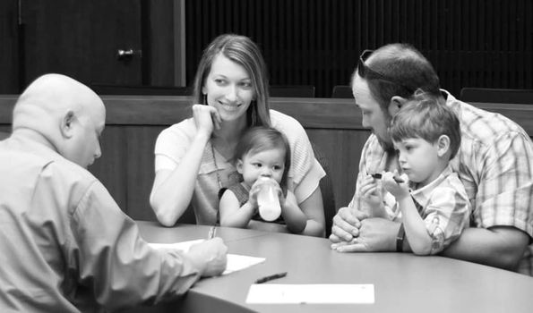 family at court signing adoption papers