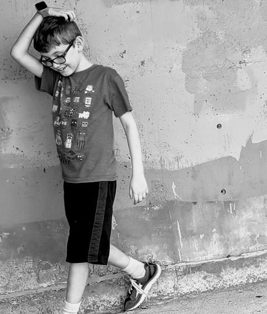 boy leaning against wall, smiling