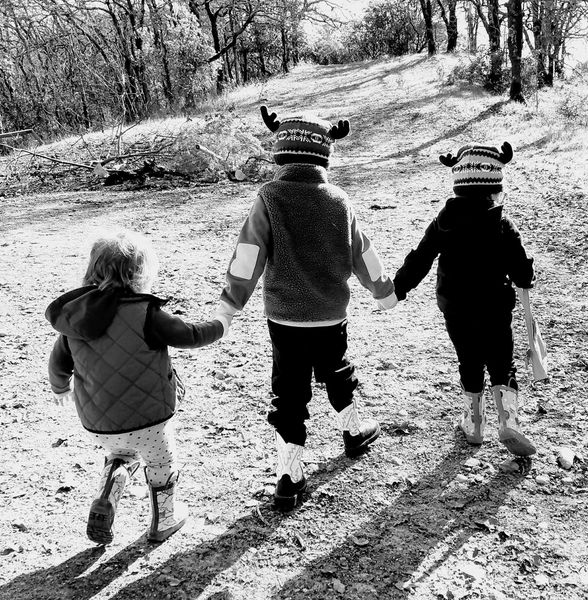 3 kids holding hands and walking